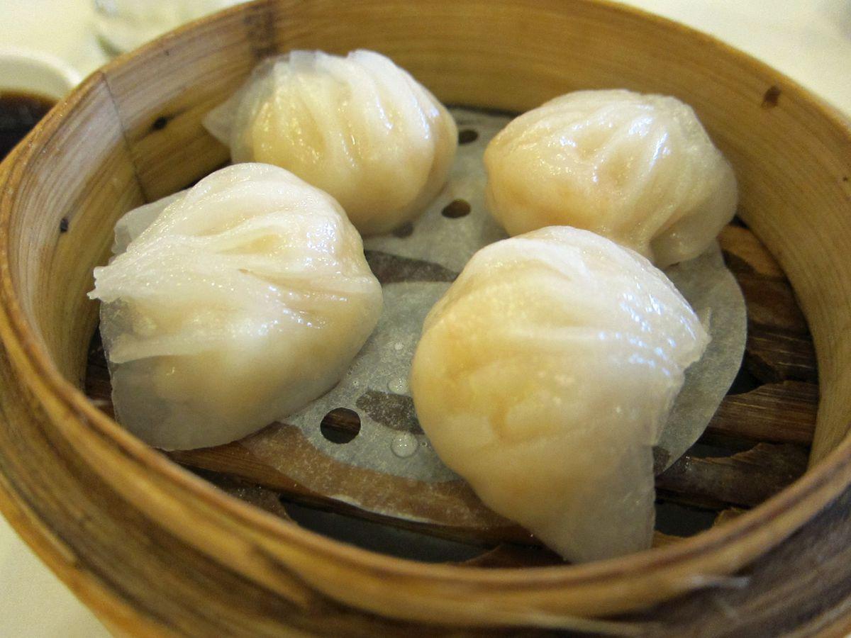 Shrimp har gow dumplings in a bamboo steamer.