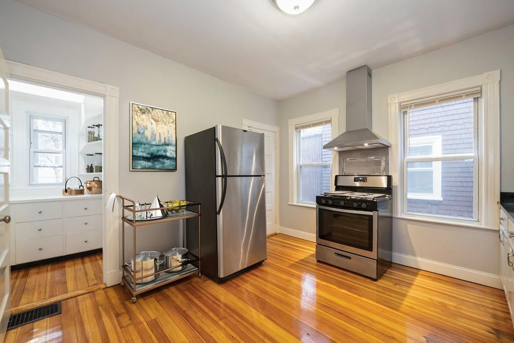 The rest of the kitchen, including a fridge and a standalone stove and oven with a vent over them.