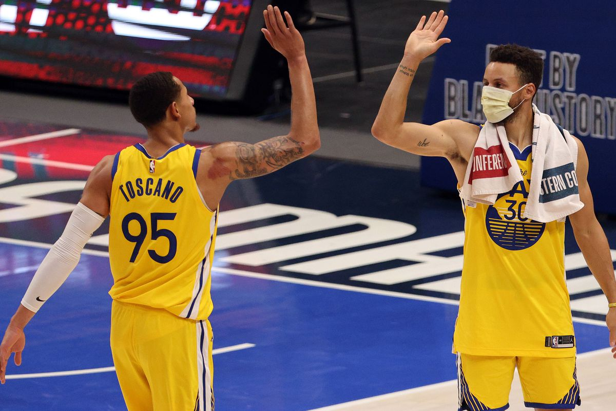 Juan Toscano-Anderson #95 and Stephen Curry #30 of the Golden State Warriors celebrate a 147-116 win against the Dallas Mavericks in the fourth quarter at American Airlines Center on February 04, 2021 in Dallas, Texas.