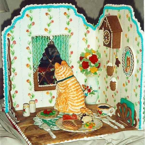 Gingerbread living room with a cat looking outside the window.