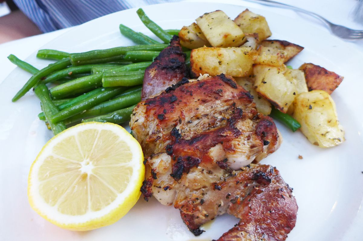 A mass of grilled rabbit with potatoes and green beans on the side.