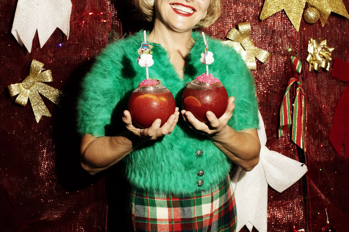 The festively adorned torso of a woman in a fuzzy green cardigan, plaid skirt, holding two bulbous drinks in front of her chest