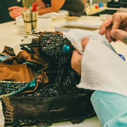 Assistant Wardrobe Manager Eric Rudy hand-sews new buttons onto the dress.