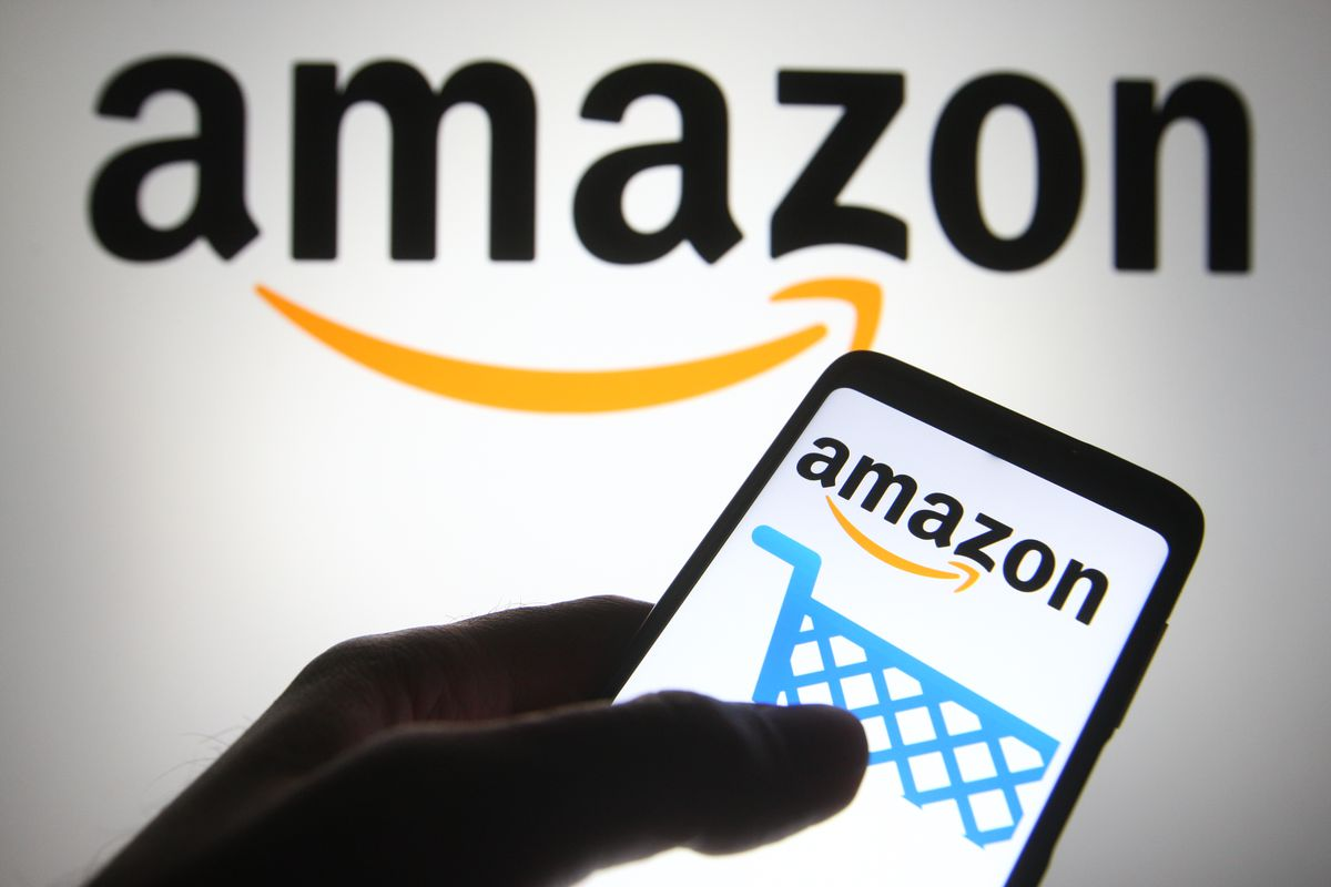 In this photo illustration the Amazon logo is seen on a...
