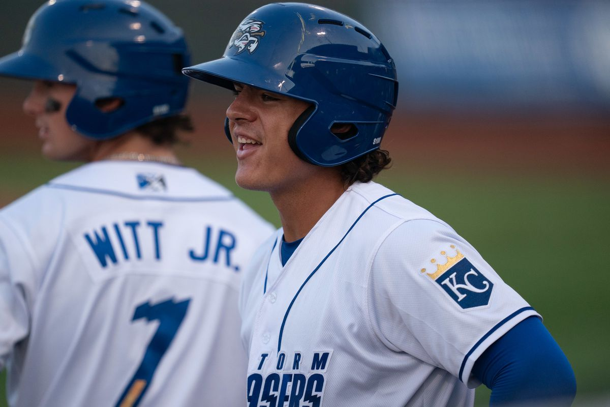 A smiling baseball player (Nick Pratto) is in the foreground in a white jersey top and a blue batting helmet. Teammate Bobby Witt, Jr. is in the background with his back turned and his last name visible on his jersey.