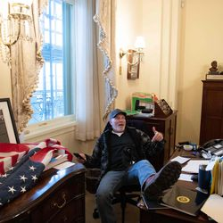 A supporter of US President Donald Trump sits inside the office of US Speaker of the House Nancy Pelosi as he protest inside the US Capitol in Washington, DC, January 6, 2021. - Demonstrators breeched security and entered the Capitol as Congress debated the a 2020 presidential election Electoral Vote Certification.