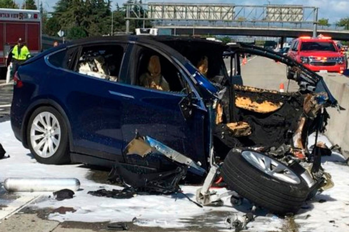 A mangled Tesla car on a highway after crashing into a highway barricade.