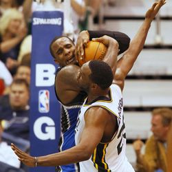 Orlando Magic's Glen Davies, left, grabs a rebound from Utah Jazz's Al Jefferson during the first half of an NBA basketball game in Salt Lake City, Saturday, April 21, 2012.