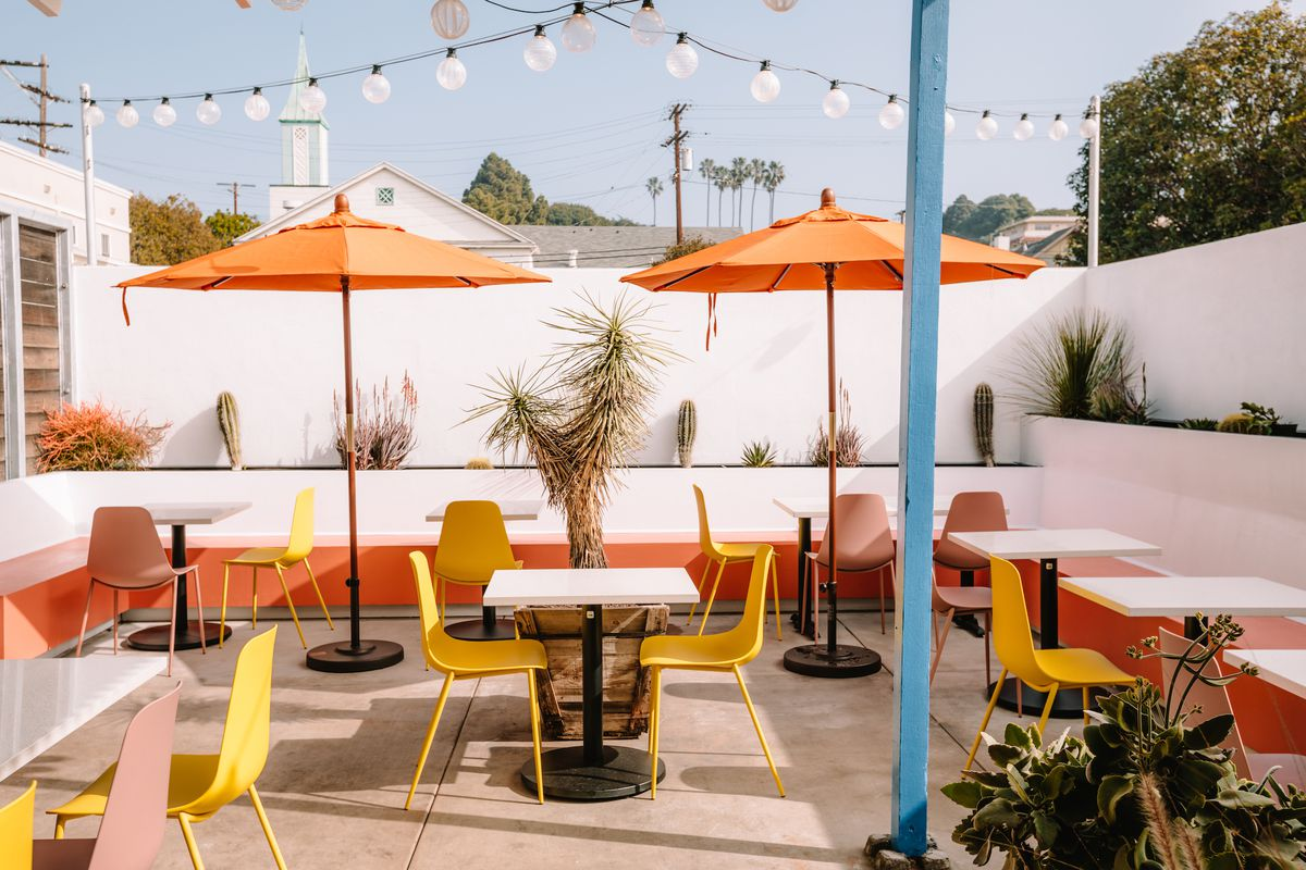 The jewel tones of an outdoor cafe with yellow tables.