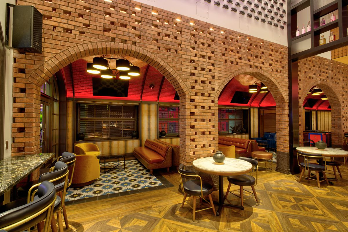 A lounge with a brick wall and leather couches