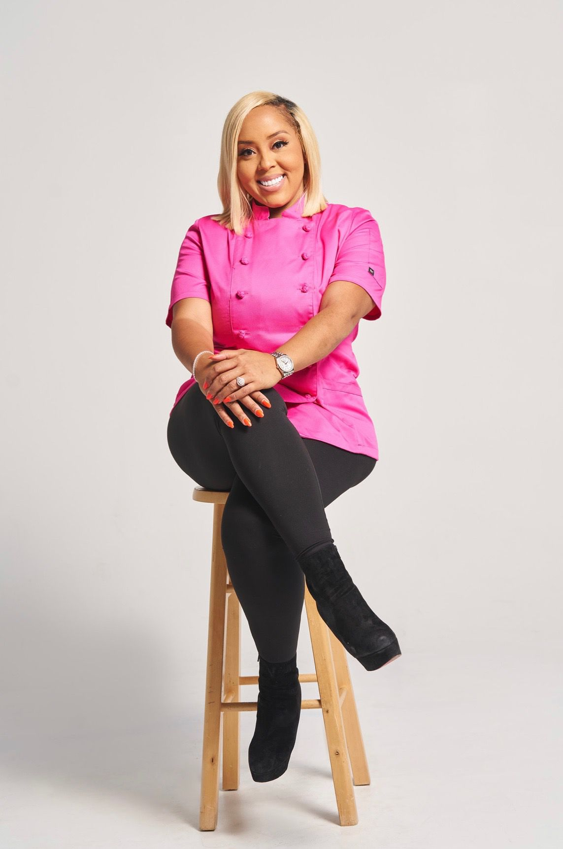 A smiling woman in a pink chef's coat sits on a stool