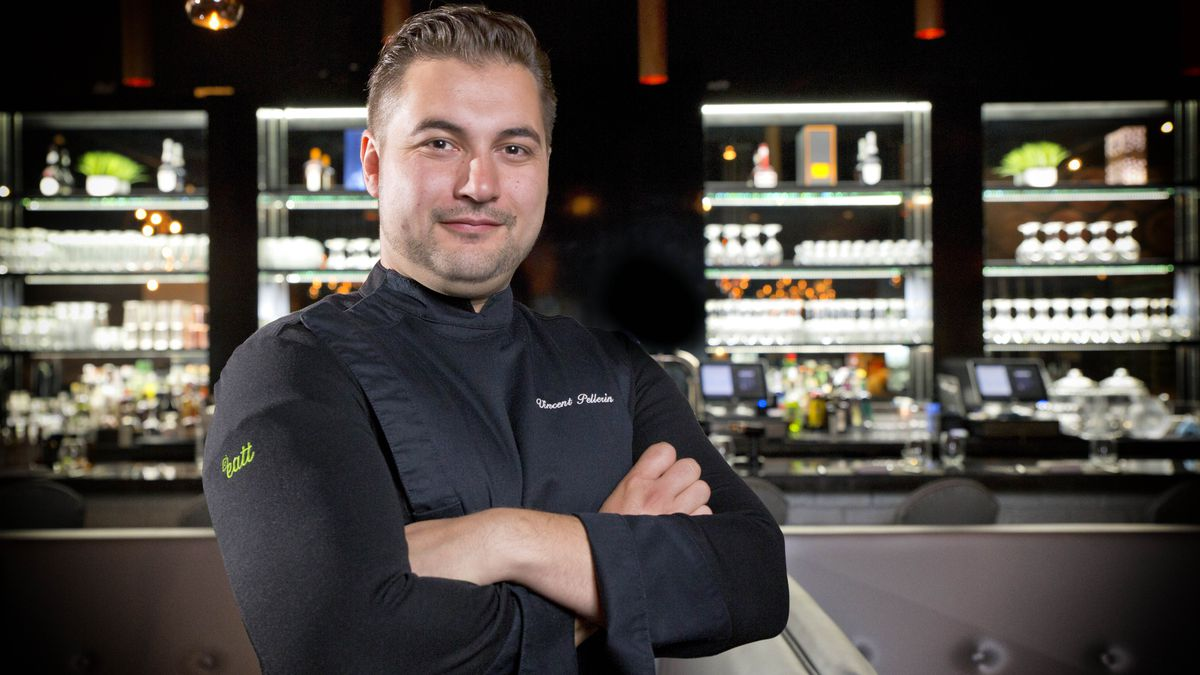 A chef wearing a black coat with his arms crossed