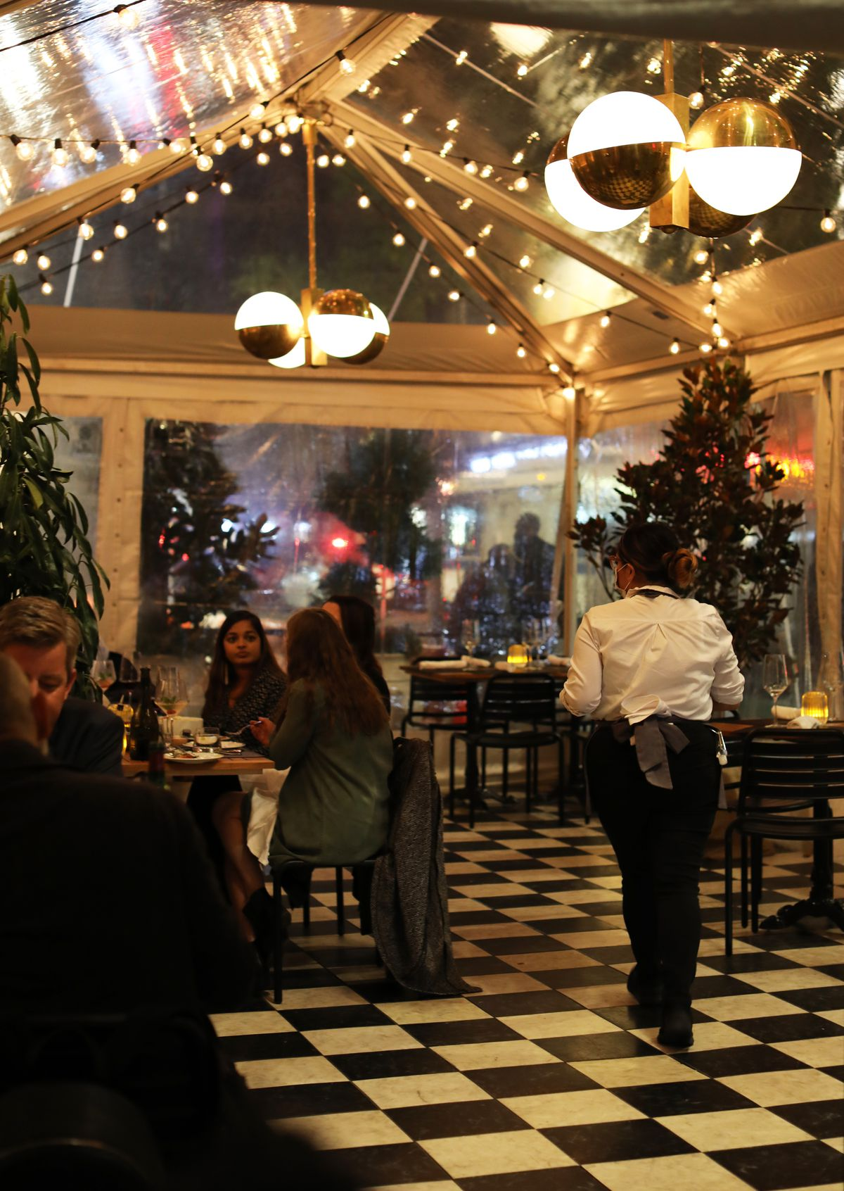 Diners sit and eat at tables positioned inside a white tent with chandeliers and string lights