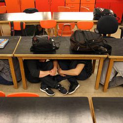 Taylorsville High School students in Steve Woolley's physics class crawl under their desks as they participate in an earthquake drill as part of The Great Utah ShakeOut, Tuesday, April 17, 2012.