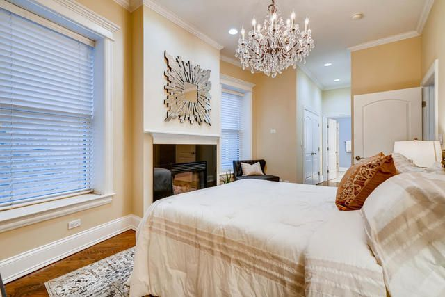 A bedroom with a chandelier, a fireplace, and a bed.