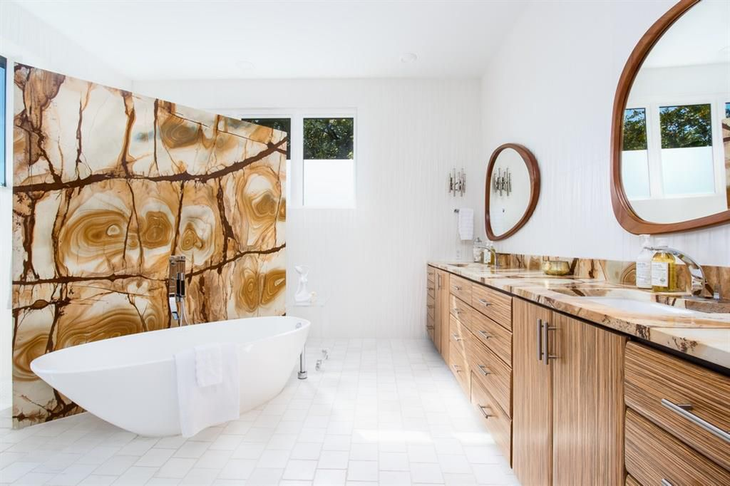 A bathroom with a modern oval freestanding tub and dramatic wall-sized marble backsplash. A full-length counter with cabinets and drawhers and two sinks lines the opposite wall. There are wood-framed mirrors in wobbly circular shapes above each sink. There's a high set of three windows in the back and possible more blocked by the tub backsplash wall.
