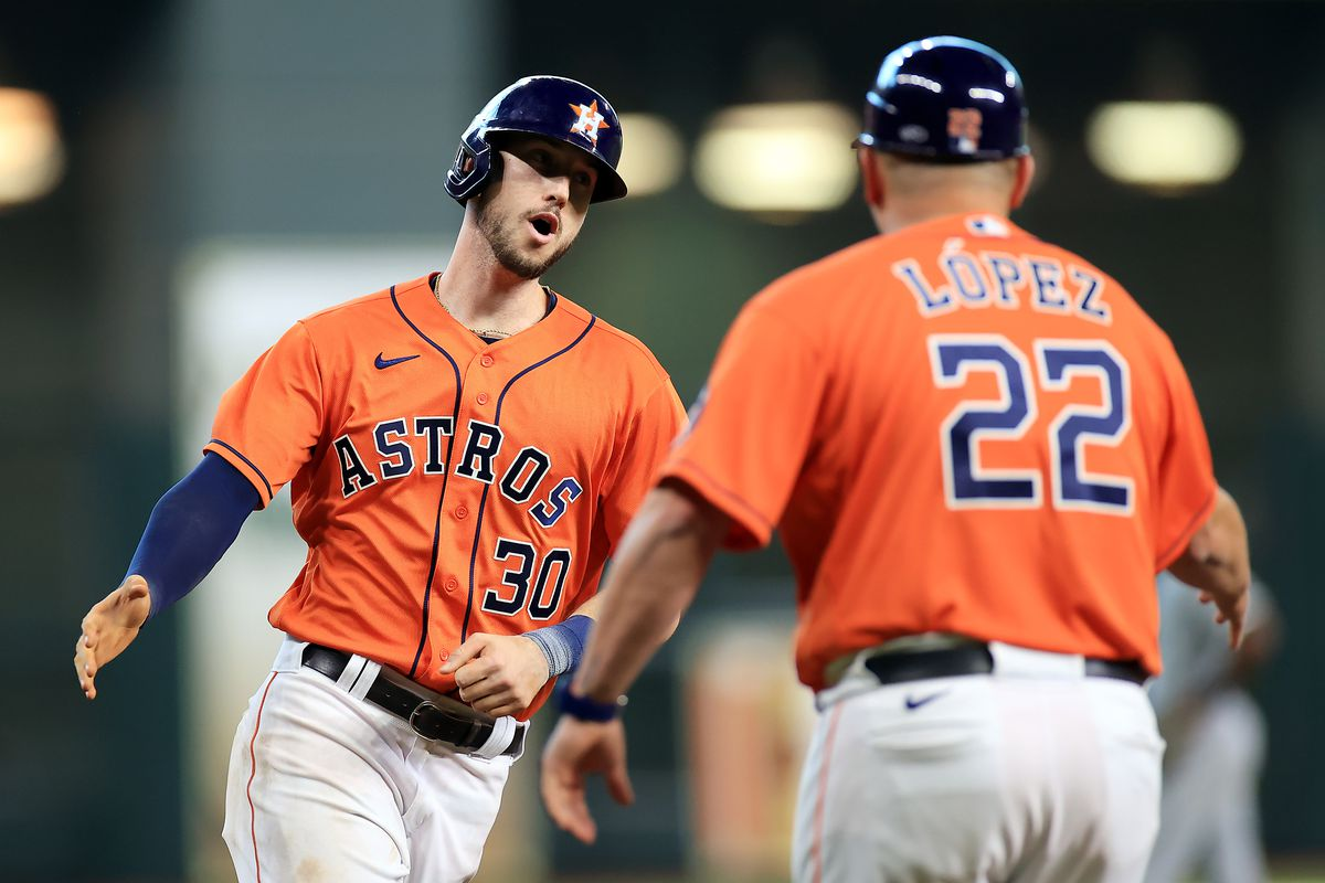 Kyle Tucker #30 of the Houston Astros is congratulated by third base coach Omar Lopez #22 as he rounds the bases after hitting a home run during the 7th inning of Game 2 of the American League Division Series against the Chicago White Sox at Minute Maid Park on October 08, 2021 in Houston, Texas.