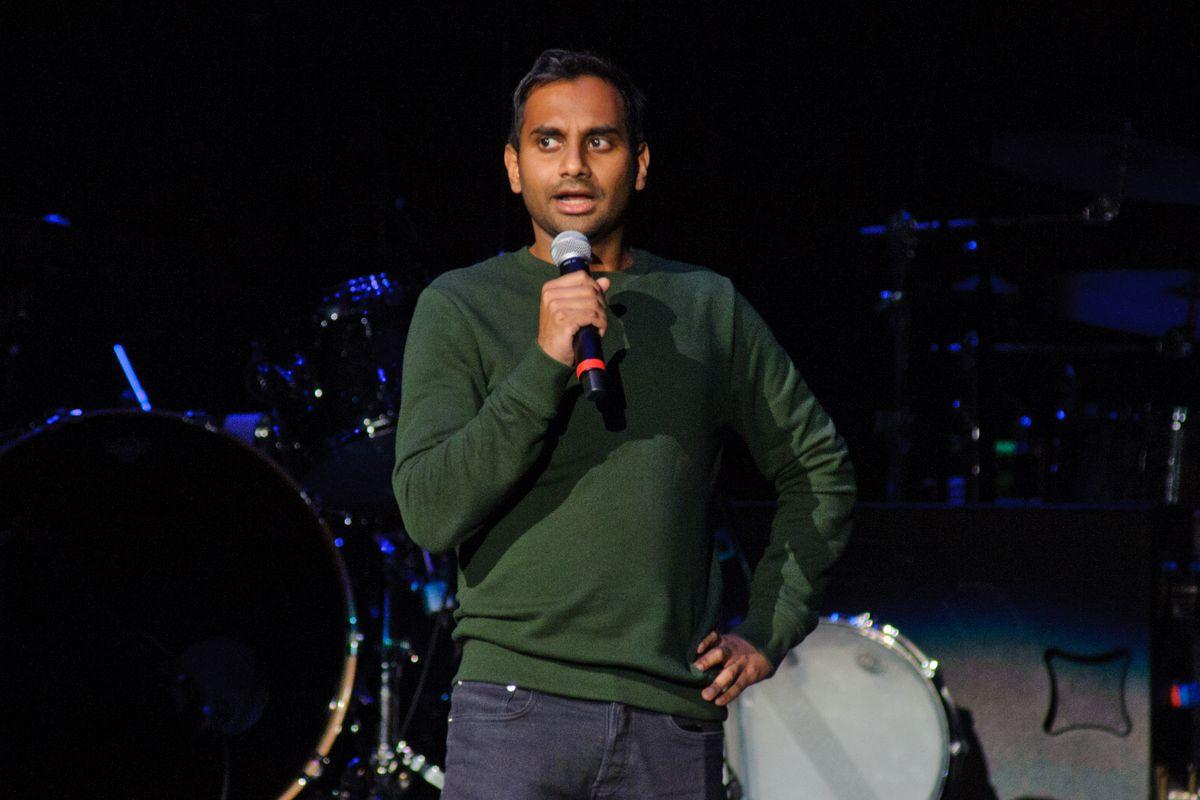 Aziz Ansari speaking into a microphone