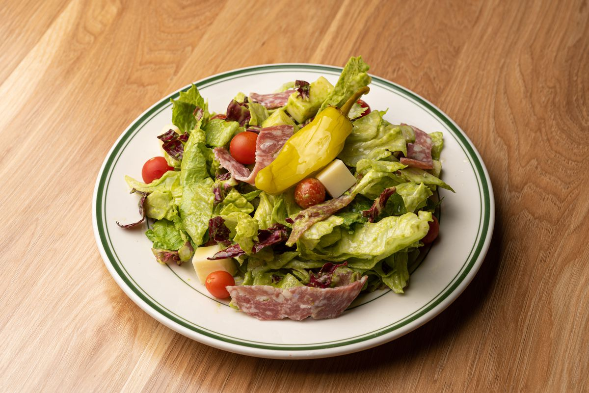 A chopped Italian salad with salami and a pepper on top.