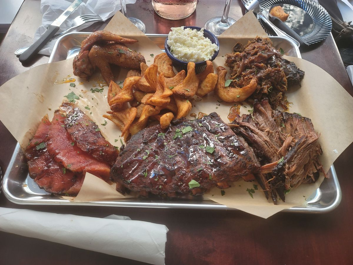 a bbq platter with watermelon, brikset, fries, and wings