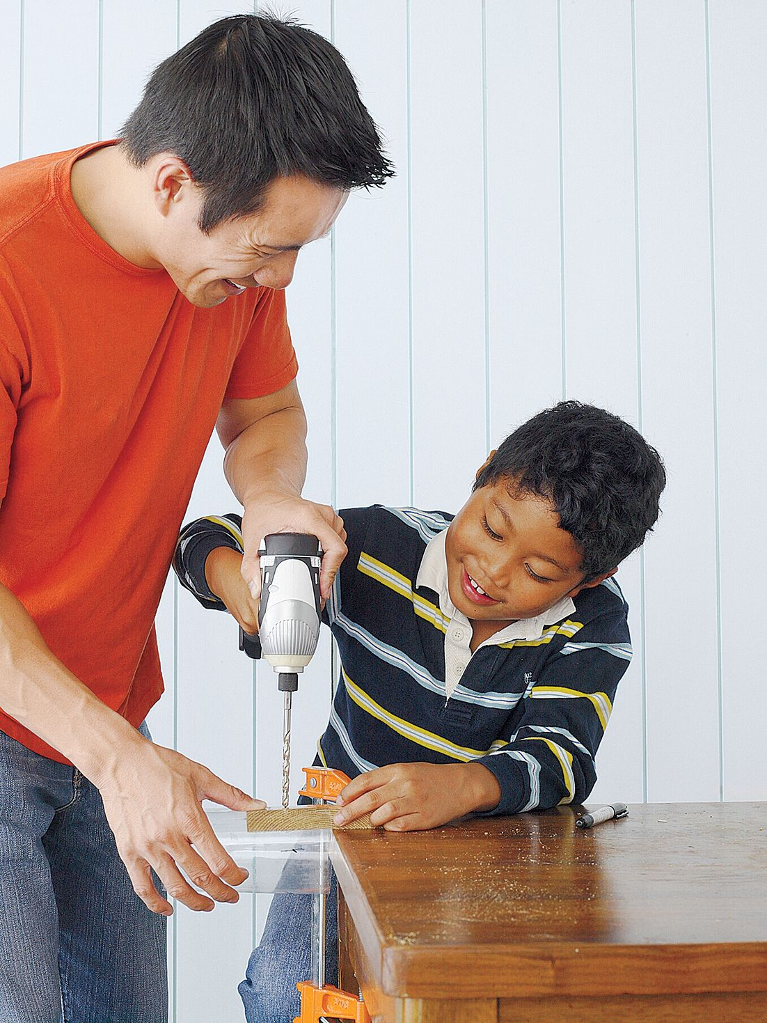 Parent and child working together to drill through wood.