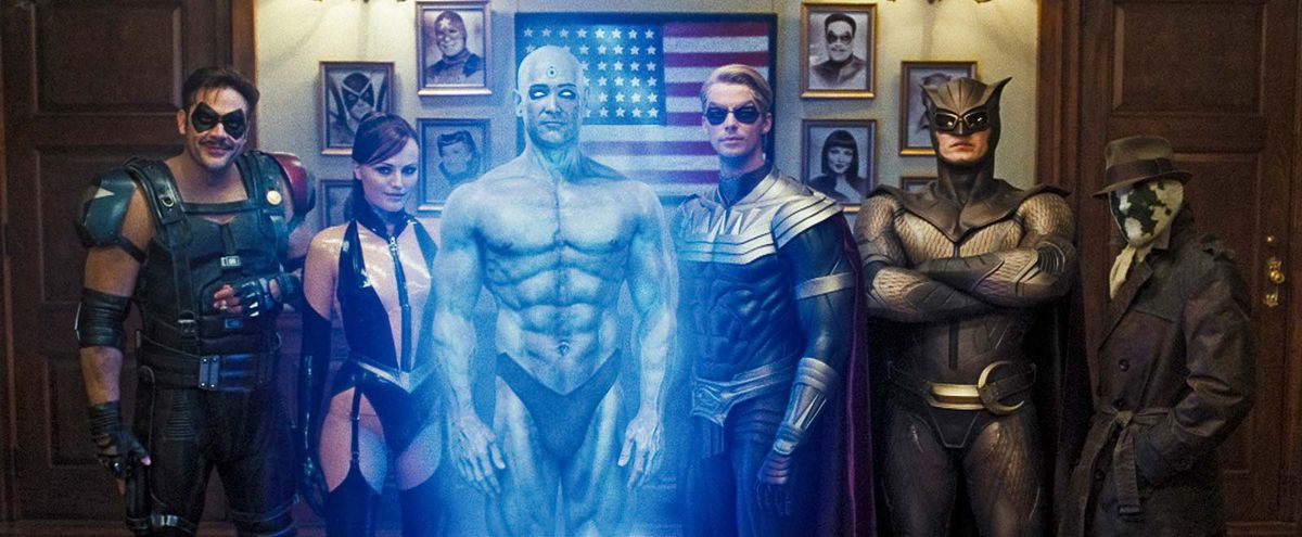 From left to right: The Comedian, Silk Spectre, Dr. Manhattan, Ozymandias, Nite Owl, and Rorschach pose for a photo in Zack Snyder's Watchmen (2009)