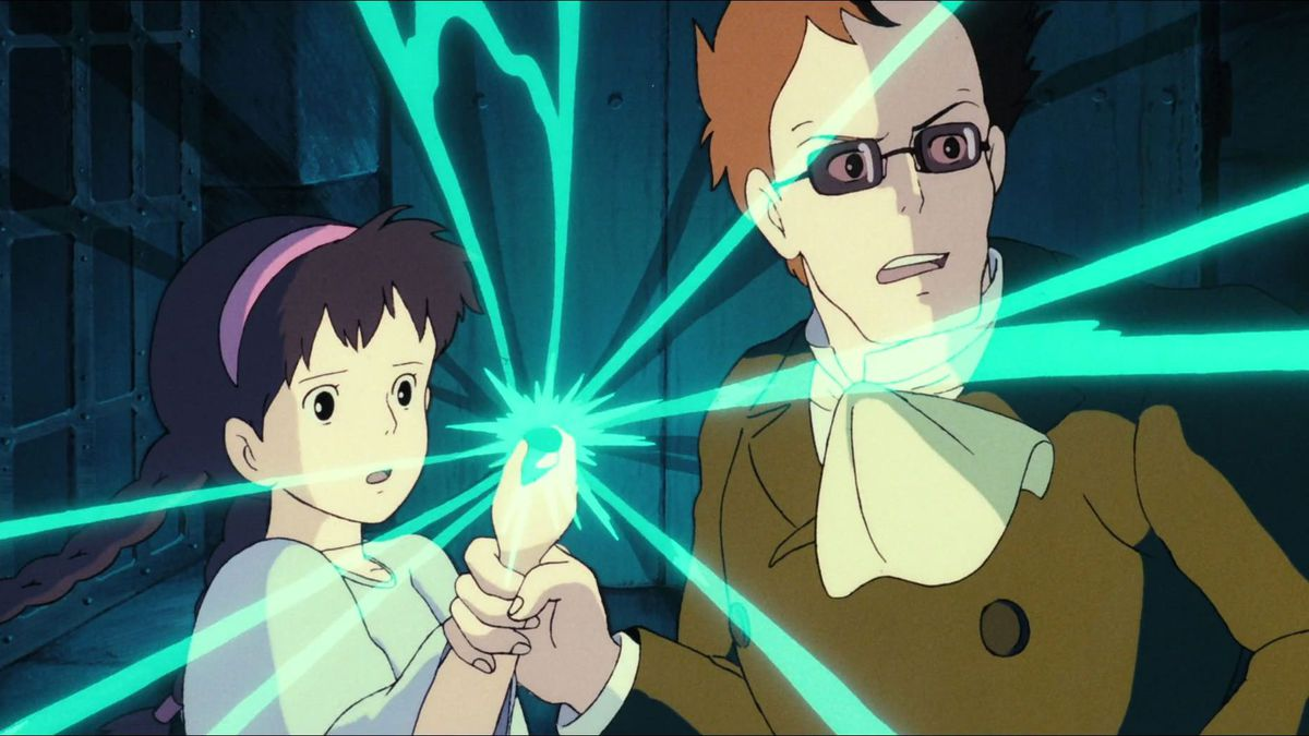 A young girl, Sheeta, and a sunglasses-wearing villain named Colonel Muska hold a crystal necklace radiating with magic energy