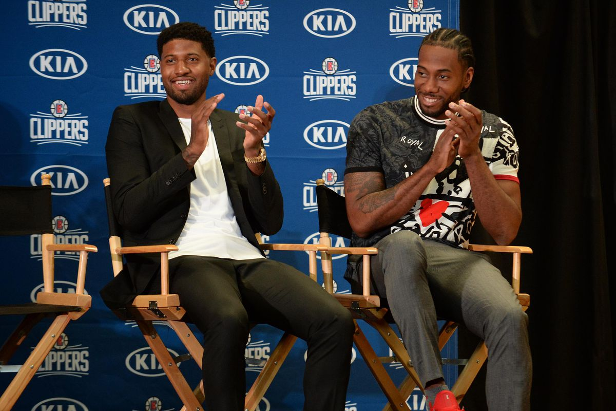 Los Angeles Clippers players Paul George and Kawhi Leonard react before being introduced to media at Green Meadows Recreation Center.