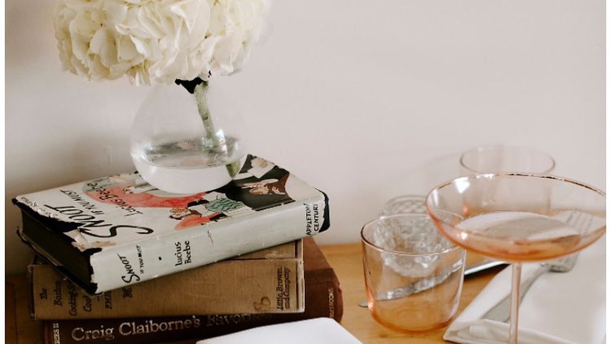 A table with three books stacked, a wide lipped pink glass, and white napkin