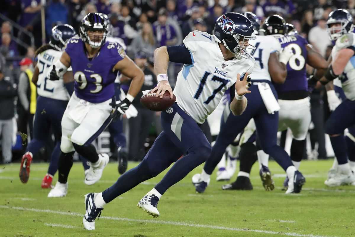 Tennessee Titans quarterback Ryan Tannehill scrambles with the ball as Baltimore Ravens nose tackle Chris Wormley chases in the fourth quarter in a AFC Divisional Round playoff football game at M&T Bank Stadium.