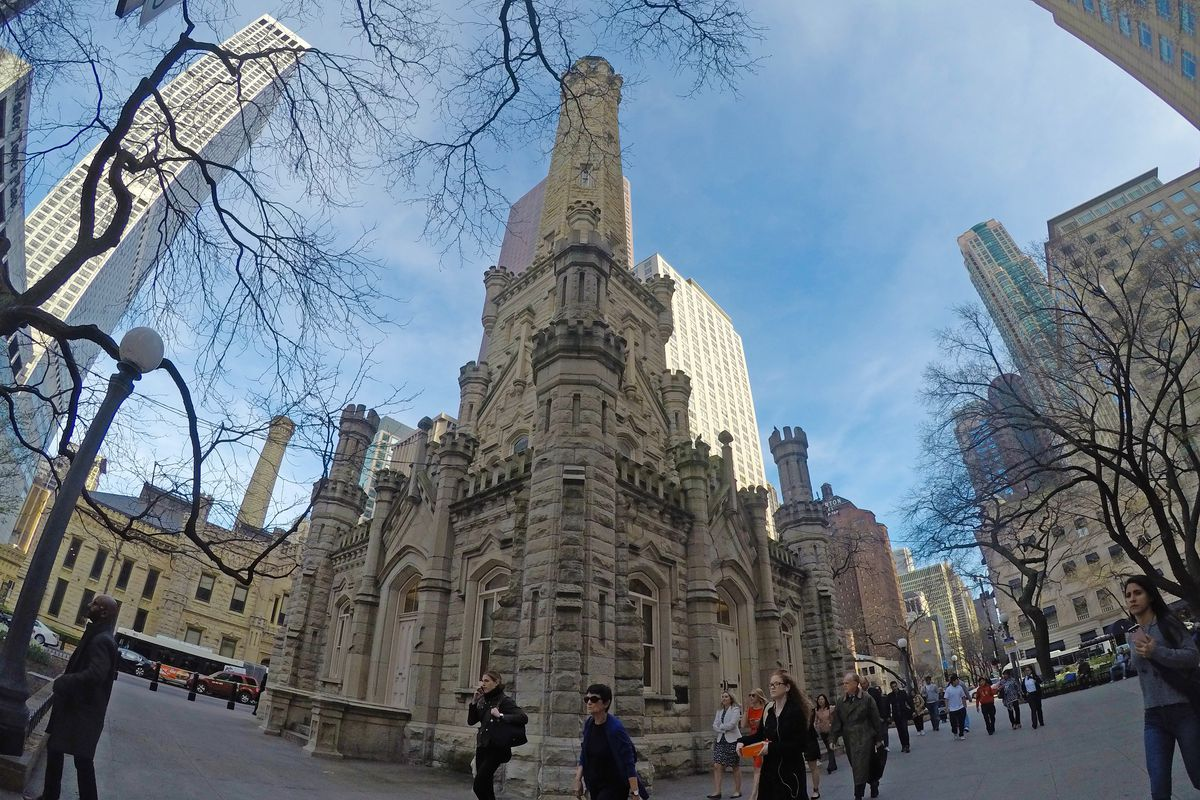With a fish eye lens, a photo of the small, square stone building with a tall spire. People walk past the structure on a busy downtown block.