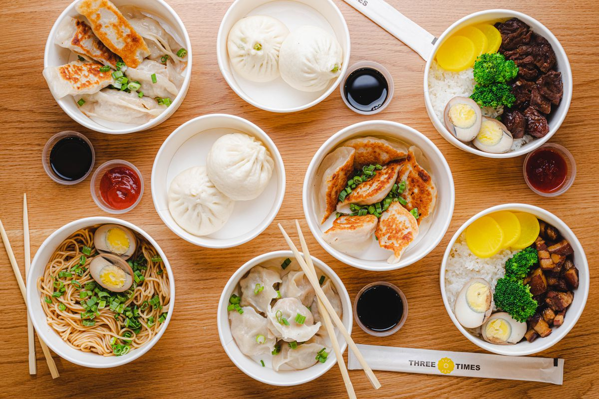 A spread of plated Chinese dishes like noodles and dumplings