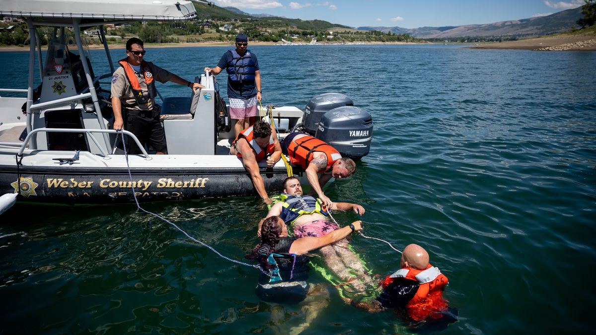 During a mock boating accident, a firefighter is pilled from the water for rescue training.