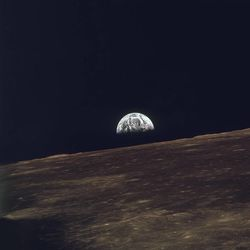 This photo, released by NASA on Dec. 29, 1968, shows the view of the rising Earth that greeted Apollo 8 astronauts as they came from behind the moon after the lunar orbit insertion burn. The Earth is about five degrees above the horizon in this photo.