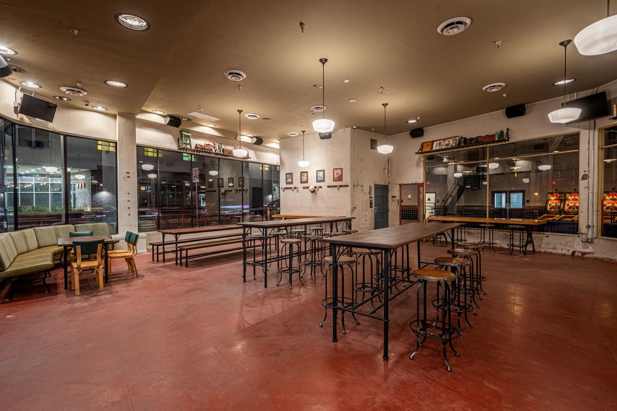Communal tables with tall metal stools inside of a redone warehouse bar at night.