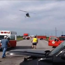 """A helicopter and emergency workers respond to  an accident scene. Rev. Patrick Dowling revealed himself as the mysterious """"angel priest"""" who prayed with 19-year-old Katie Lentz, after reading a National Catholic Register article about the Missouri accident that occurred last week."""