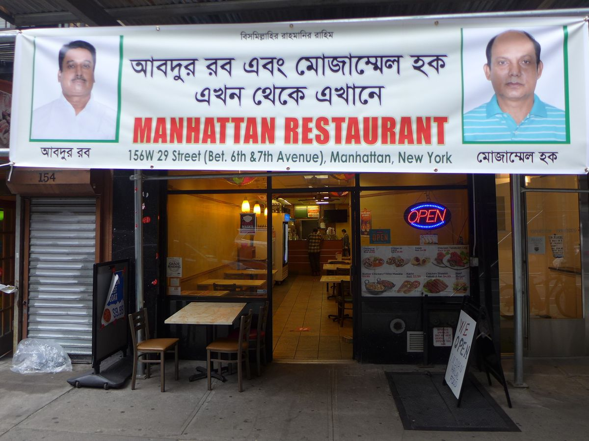 A banner in front of the storefront proclaims the name of the restaurant with head shots of the two proprietors.
