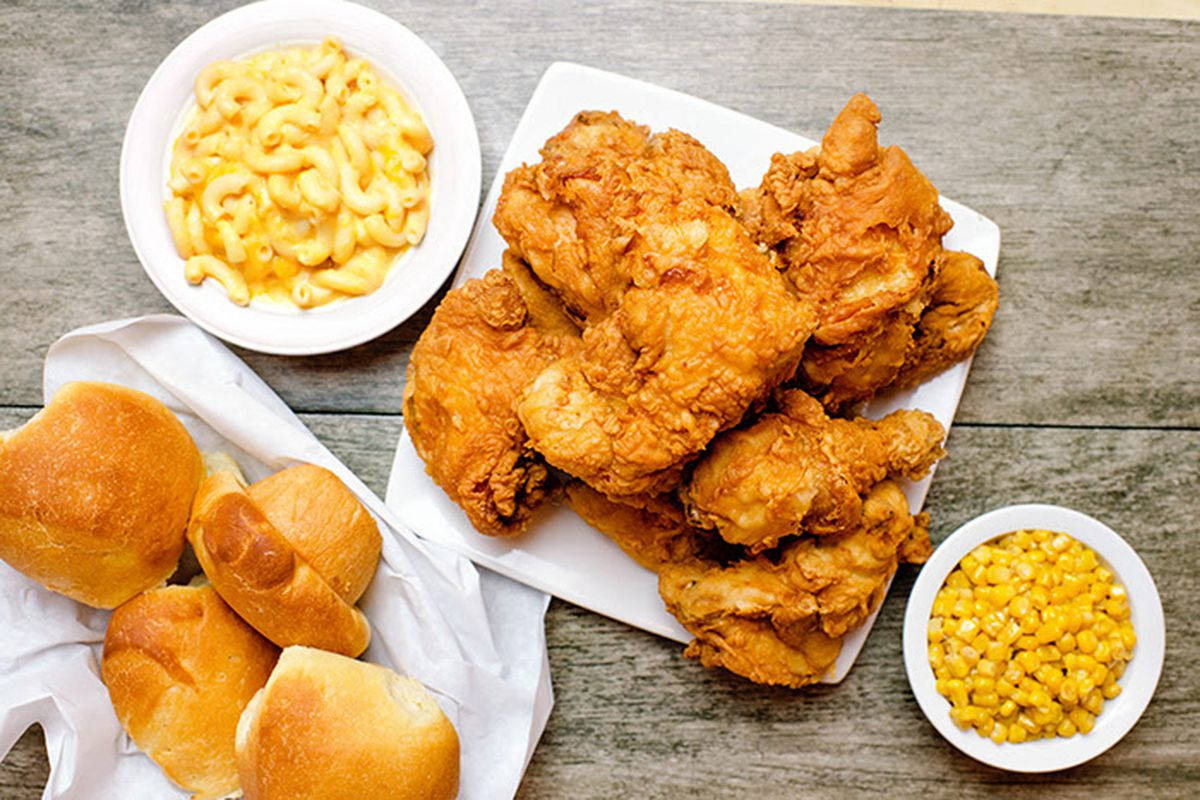 A platter of bone-in chicken, rolls, beans, and macaroni and cheese sit on a grey wooden table at Ezell's.