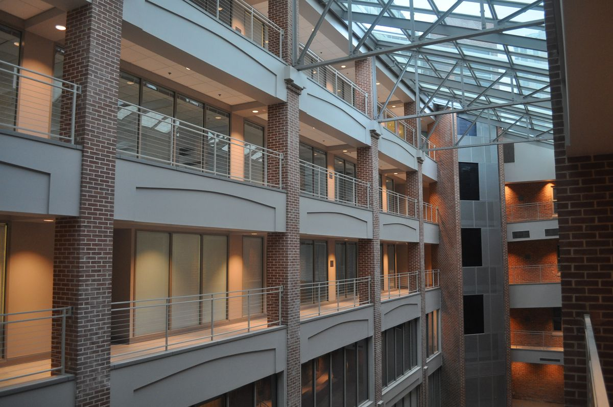 Stacked corridors of offices look out over a five-story atrium with glass roof.