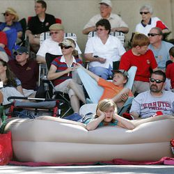 Madison Bawden, 9, of Taylorsville, gets sleepy on her air mattress at the Days of '47 Parade in Salt Lake City Saturday. Madison had been camped out on Second East since Friday morning.