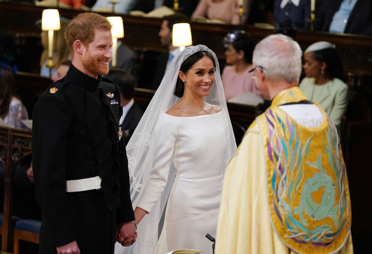 Markle and Prince Harry stand at the altar holding hands.