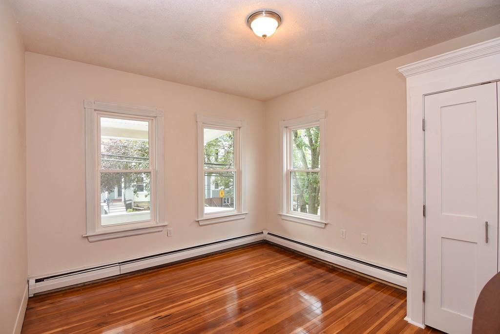 An empty bedroom with three windows, including two on one wall, and baseboard heating.