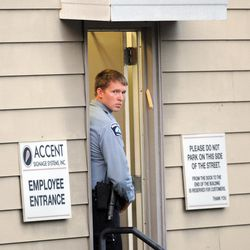 """A Minneapolis police officer stands at the entrance of Accent Signage Systems as police investigate a shooting at the business that police say left """"several"""" people dead, including the shooter, who was found dead from a self-inflicted gunshot wound, Thursday, Sept. 27, 2012 in Minneapolis."""