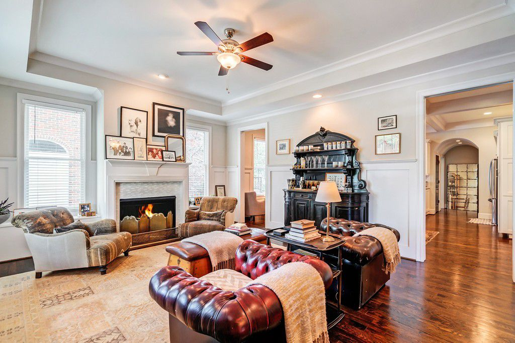 A white family room with old furniture and a ceiling fan.