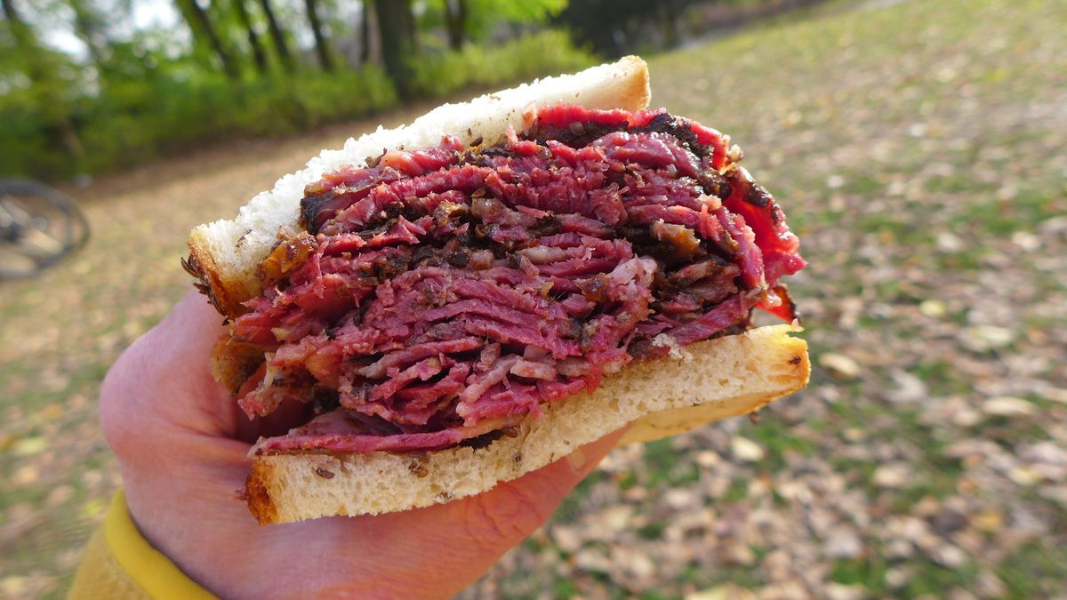 A hand holds a giant sandwich stuffed with red meat against a Central Park backdrop.