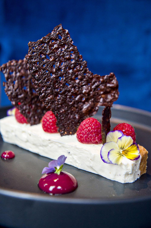 The white cheesecake, white chocolate, and lavender cheesecake with raspberry mint gel, dark chocolate crisps, and fresh raspberries at Pistol Whip.