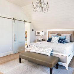 A sliding barn door opens to provide access from the main bedroom to the adjoining dressing closet and bath.