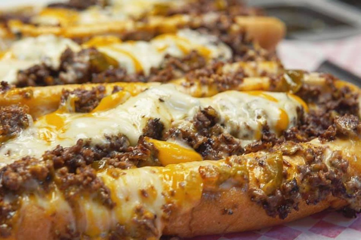 Two cheesesteaks sandwiches oozing with melted cheese and ground beef