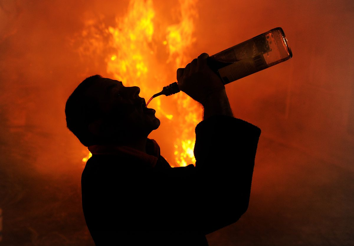 A man drinks alcohol in front of a huge fire.