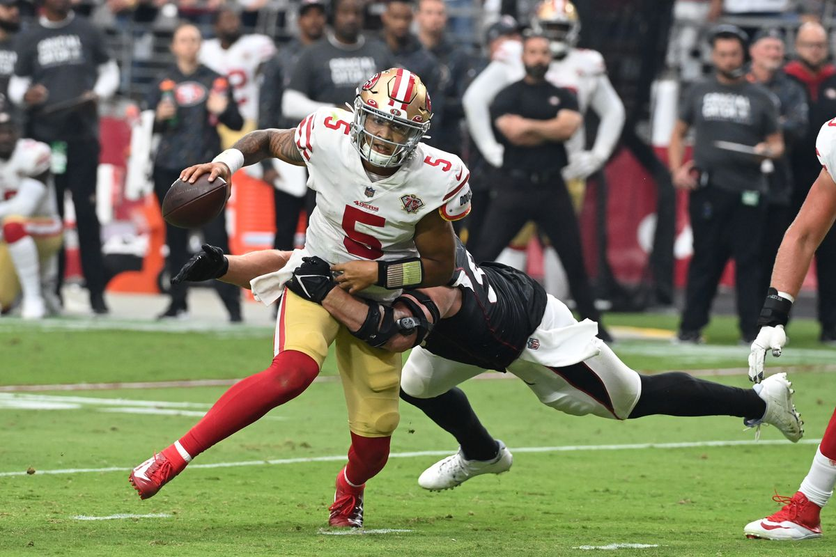 Trey Lance #5 of the San Francisco 49ers attempts to break a tackle by JJ Watt #99 of the Arizona Cardinals at State Farm Stadium on October 10, 2021 in Glendale, Arizona.